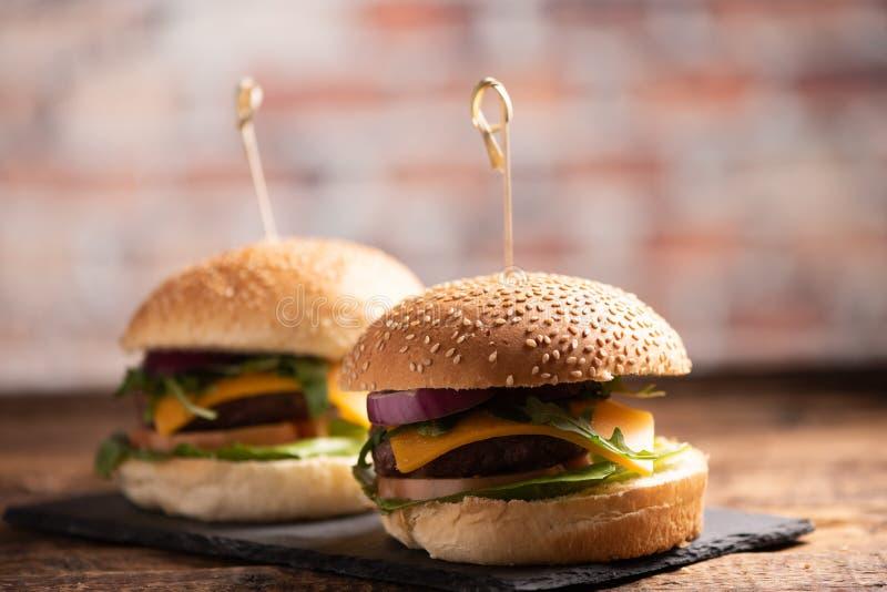 Hamburger avec de la laitue, fromage de cheddar, oignons, tomate photos stock