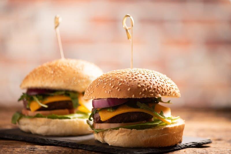 Hamburger avec de la laitue, fromage de cheddar, oignons, tomate image libre de droits