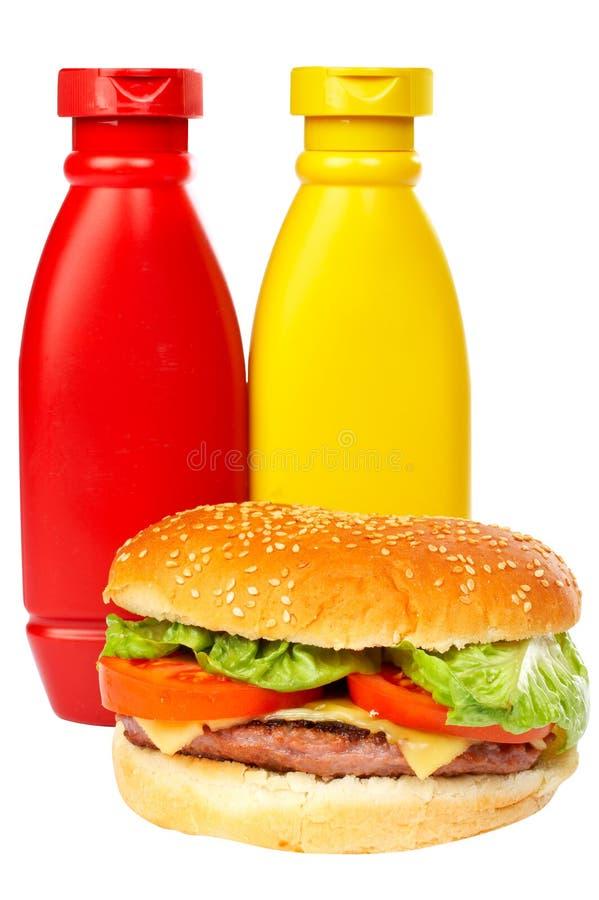 Hamburger avec des bouteilles de moutarde et de ketchup photographie stock libre de droits