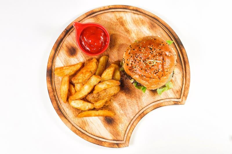 Hamburger avec des cales et souce sur le rond en bois photos libres de droits
