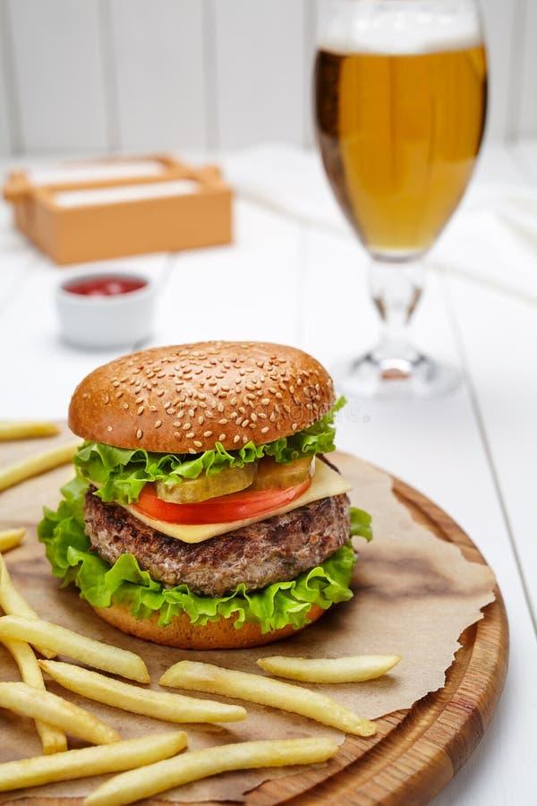 Hamburger avec du boeuf, la tomate, le fromage, la salade et les fritures marbrés grillés image libre de droits