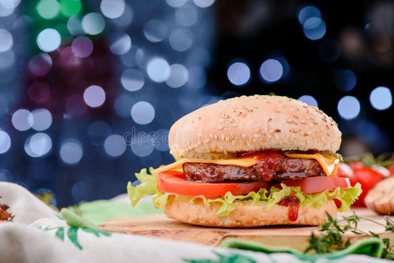 Hamburger avec la côtelette juteuse, les tomates, le fromage, la laitue et la sauce rouge sur le conseil en bois contre la guirla photographie stock libre de droits