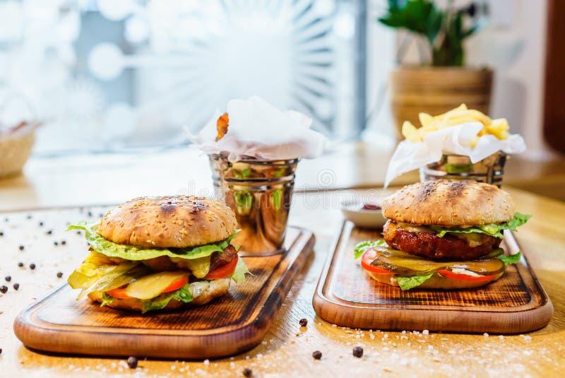 Hamburger avec le saindoux, le fromage de veau et la laitue Nourriture traditionnelle américaine Sur un fond en bois image libre de droits