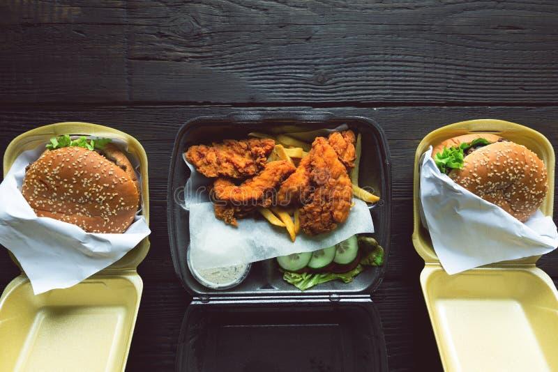 Hamburger, batatas fritas e frango frito em uns recipientes afastados no fundo de madeira Entrega do alimento e conceito do fast  imagens de stock