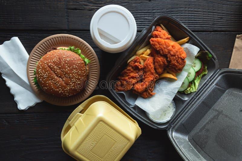 Hamburger, batatas fritas e frango frito em uns recipientes afastados no fundo de madeira Entrega do alimento e conceito do fast  fotos de stock