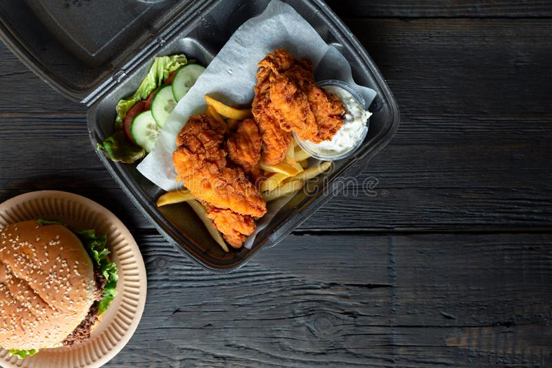 Hamburger, batatas fritas e frango frito em uns recipientes afastados no fundo de madeira Entrega do alimento e conceito do fast  imagens de stock royalty free