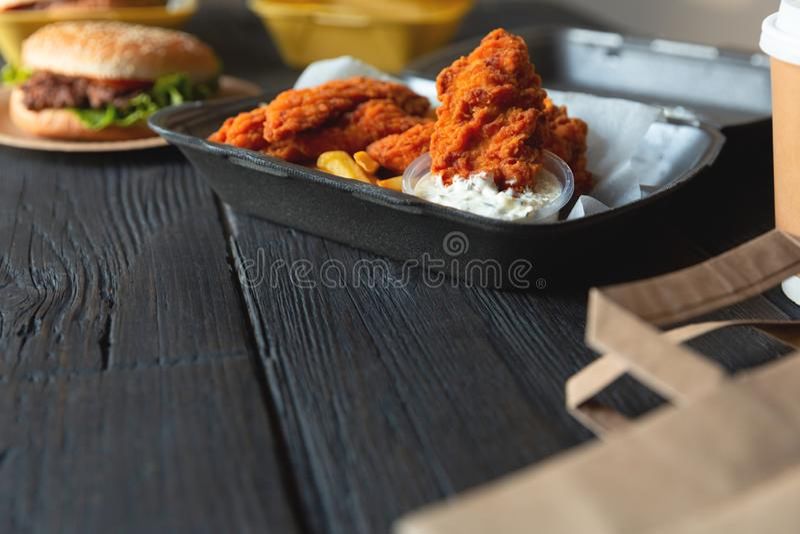 Hamburger, batatas fritas e frango frito em uns recipientes afastados no fundo de madeira Entrega do alimento e conceito do fast  imagem de stock