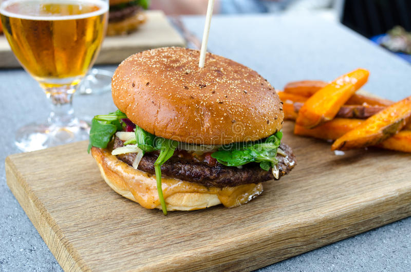 Hamburger and beer. On a wooden plank royalty free stock images
