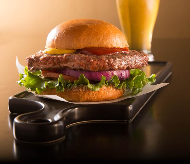 Hamburger on a brioche bun with a beer. Hamburger half pound of beef on a brioche bun on a black plate with a beer royalty free stock photo