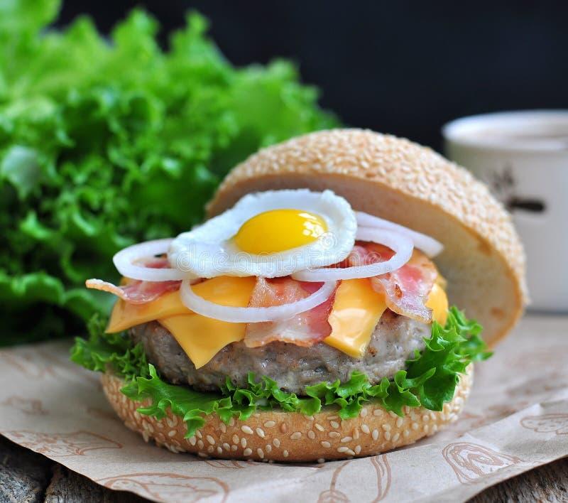 Hamburger, Burger mit gegrilltem Rindfleisch, Ei, Käse, Speck und Gemüse stockfoto