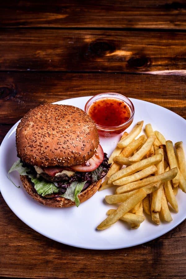 Hamburger caldo con insalata verde, i pomodori, la cotoletta succosa con le patate fritte e la salsa fotografia stock libera da diritti