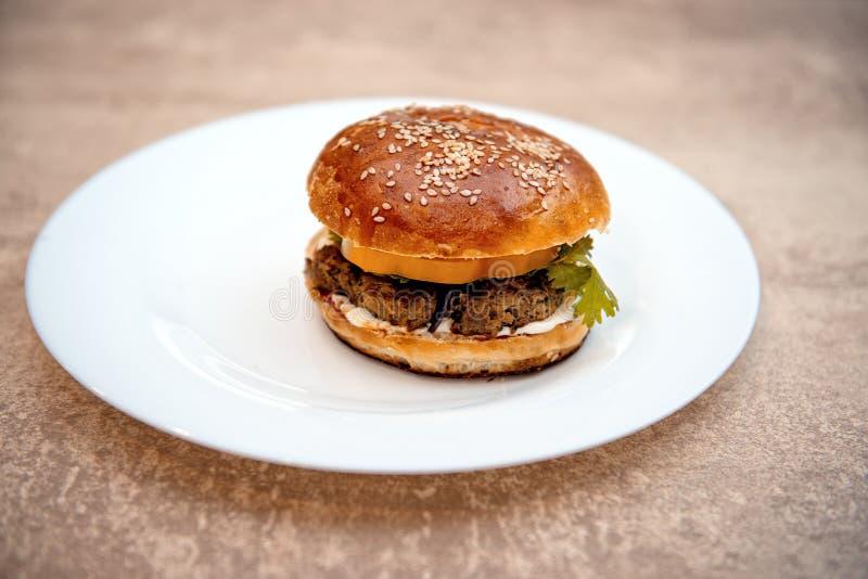 Hamburger casalingo con gli ortaggi freschi sul piatto bianco fotografia stock