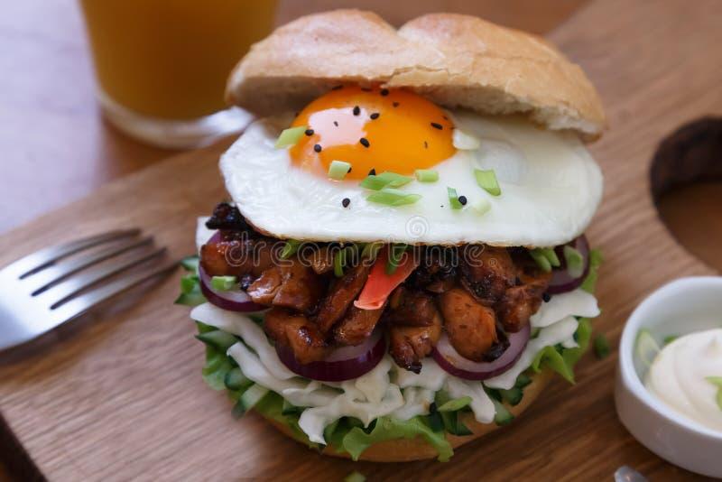 Hamburger casalingo con l'uovo fritto e le fritture piccanti sul bordo di legno immagini stock libere da diritti