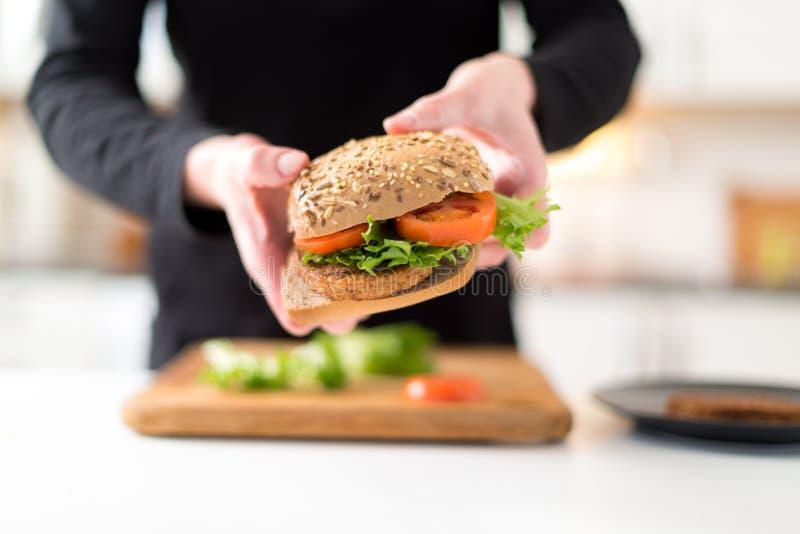 Hamburger casalingo della verdura della tenuta della donna fotografia stock libera da diritti
