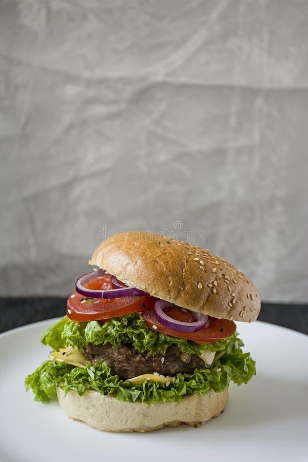 Hamburger casalingo fresco su un piatto bianco Alimento non sano immagine stock
