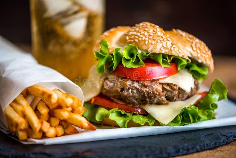 Hamburger caseiro com legumes frescos e bebida com gelo imagem de stock