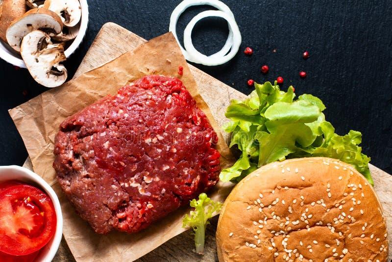 Hamburger caseiro do conceito do alimento da preparação na placa de madeira com fotografia de stock