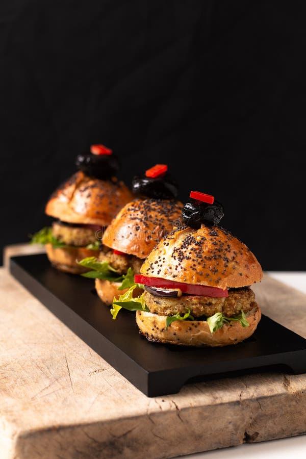 Hamburger caseiros do quinoa do vegetariano do conceito saudável do alimento na placa preta com espaço da cópia imagem de stock royalty free