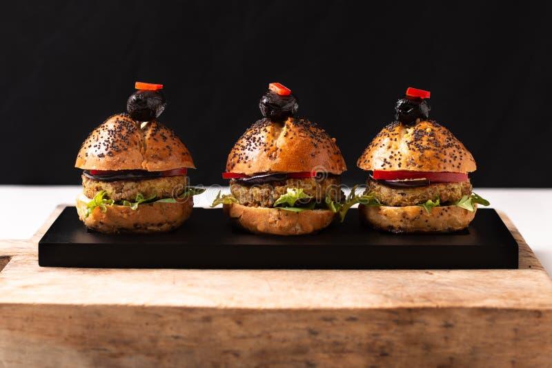 Hamburger caseiros do quinoa do vegetariano do conceito saudável do alimento na placa preta com espaço da cópia imagens de stock
