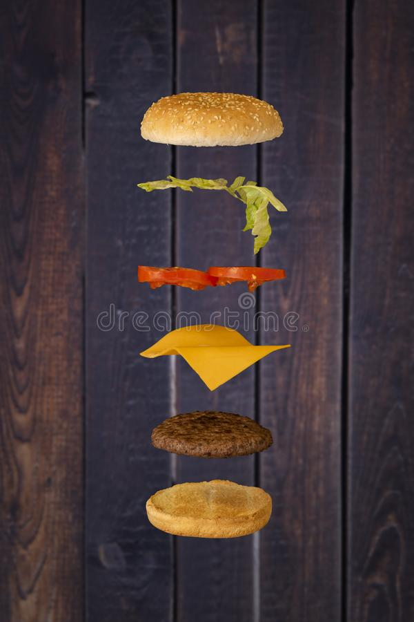 Hamburger che galleggia con il fondo di legno fotografia stock
