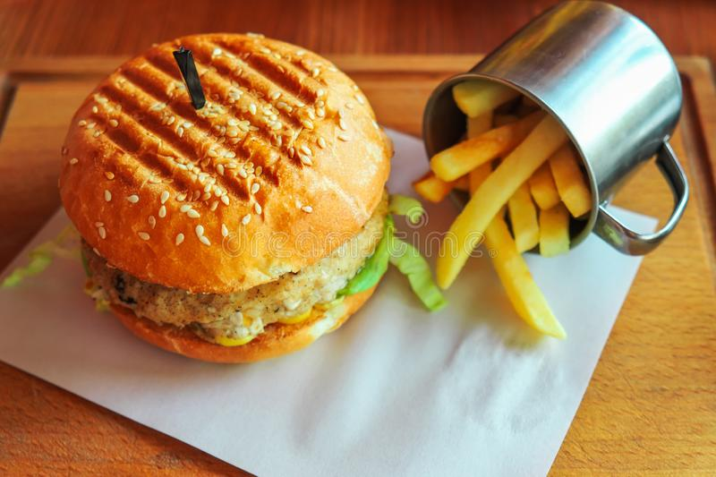 Hamburger with cheese and chop and a cup of deep fried potatoes. royalty free stock photos
