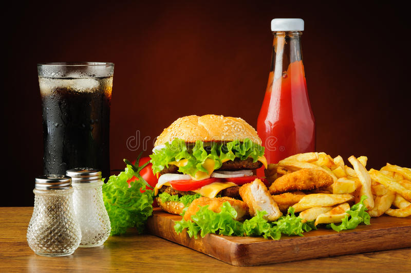 Hamburger, chicken nuggets, french fries, cola and ketchup stock image