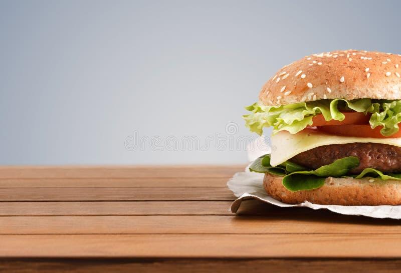 Hamburger classico del manzo sulla fine di legno della tavola su backgorund grigio fotografie stock libere da diritti