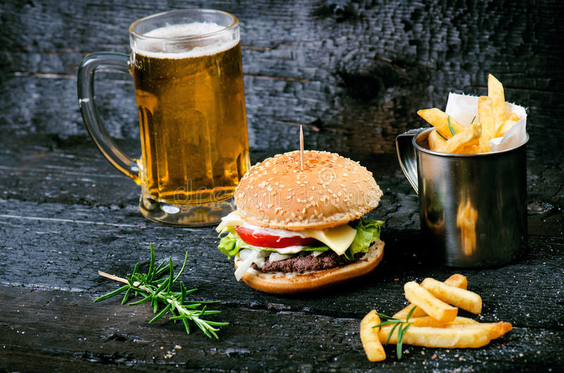 Hamburger com batatas fritas, cerveja em uma tabela de madeira queimada, preta Refeição do fast food O Hamburger caseiro consiste fotografia de stock