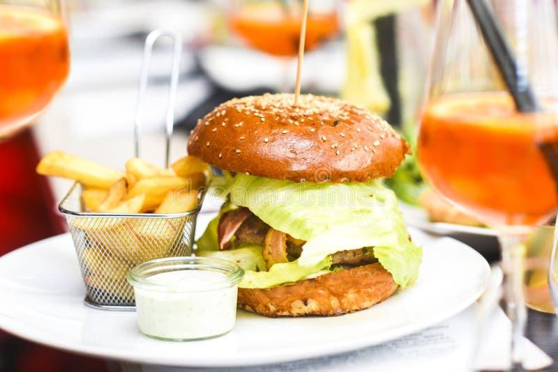 Hamburger com fritadas em uma placa em um restaura belamente servido fotos de stock