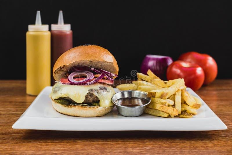 Hamburger con formaggio, la cipolla, il bacon, il sottaceto, le patate fritte, il bbq, il ketchup e la maionese immagini stock libere da diritti