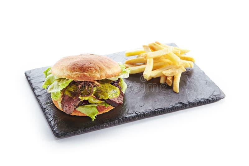 Hamburger con il contorno dell'arrosto di manzo, della senape e delle patate fritte fotografia stock libera da diritti
