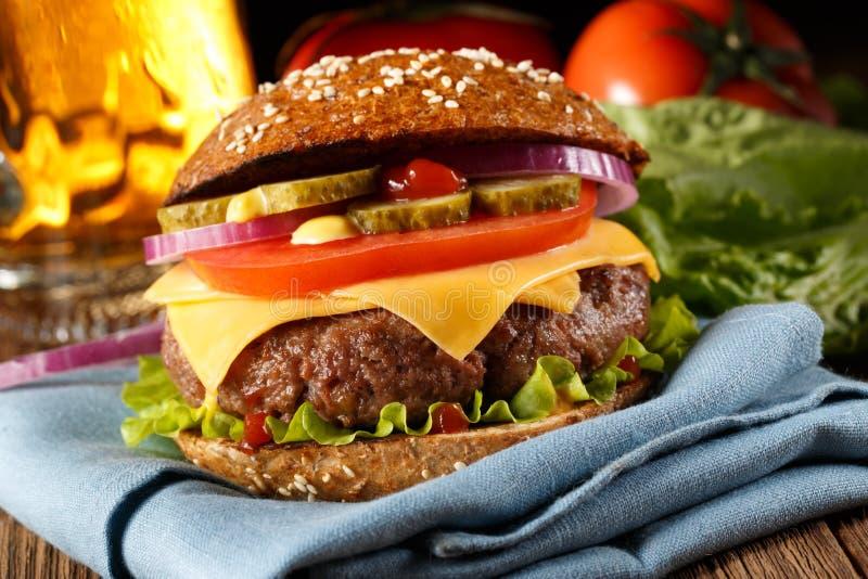 Hamburger con la fine della birra su fotografie stock