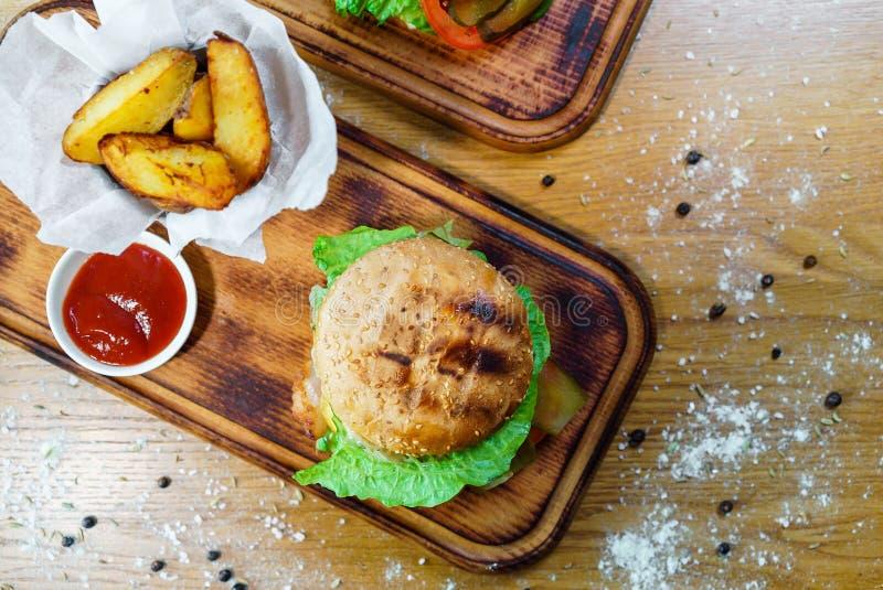 Hamburger con lardo, il formaggio del vitello e la lattuga Alimento tradizionale americano Su una priorità bassa di legno immagini stock libere da diritti