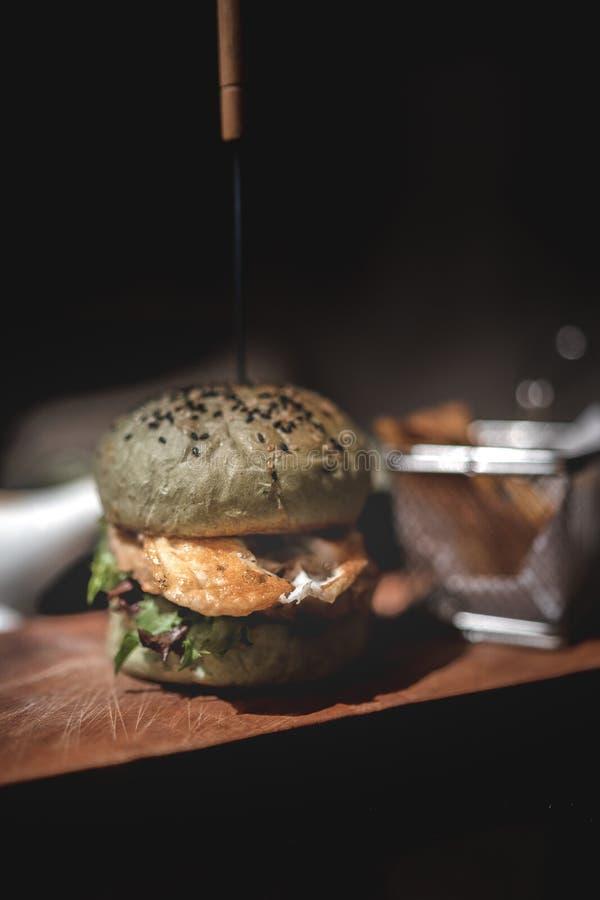 Hamburger con le fritture sul piatto di legno fotografia stock libera da diritti