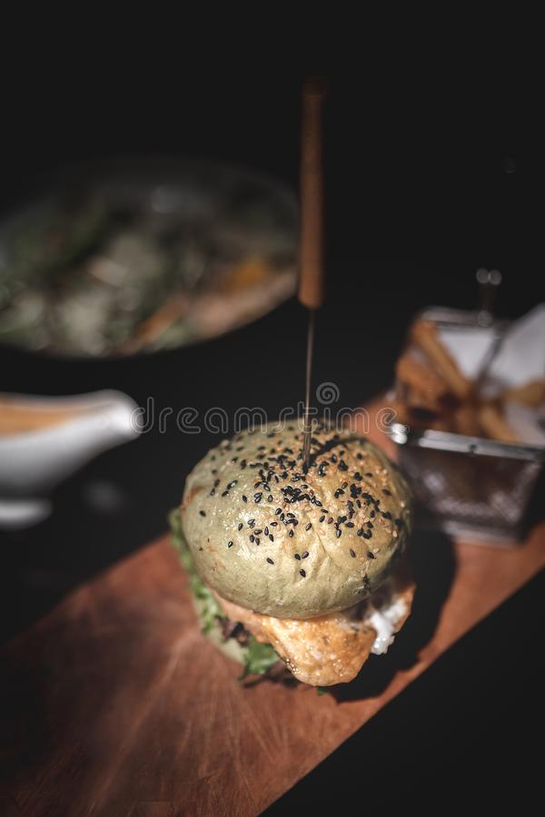 Hamburger con le fritture sul piatto di legno fotografie stock libere da diritti