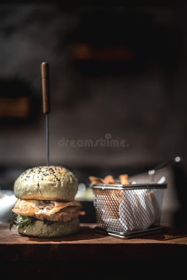 Hamburger con le fritture sul piatto di legno immagini stock libere da diritti