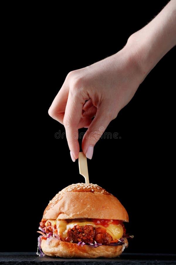 Hamburger con lo spiedo su legno le mani femminili tengono lo spiedo fotografia stock