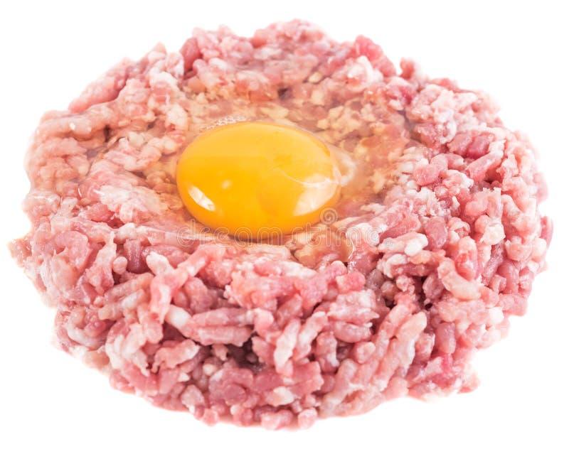 Hamburger crudo con il tuorlo d'uovo del pollo isolato immagine stock libera da diritti
