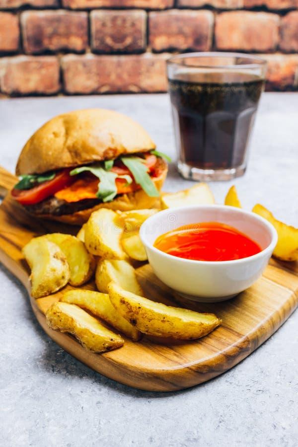 Hamburger délicieux de gril avec les pommes de terre frites image libre de droits
