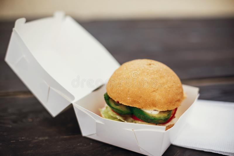 Hamburger délicieux de vegan avec l'avocat et les betteraves dans le plateau de carton sur la table en bois au festival de nourri images libres de droits