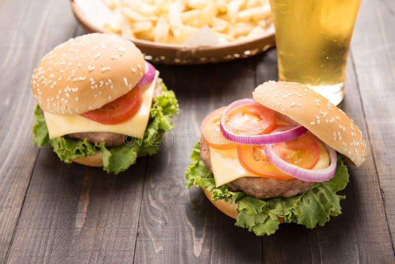 Hamburger de BBQ avec les pommes frites et la bière sur le backgroun en bois photos libres de droits