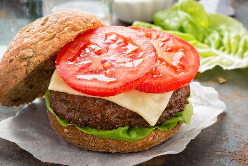 Hamburger de bifteck avec de la laitue verte, tranches de tomates et oignons grillés - les piments doux plongent images libres de droits