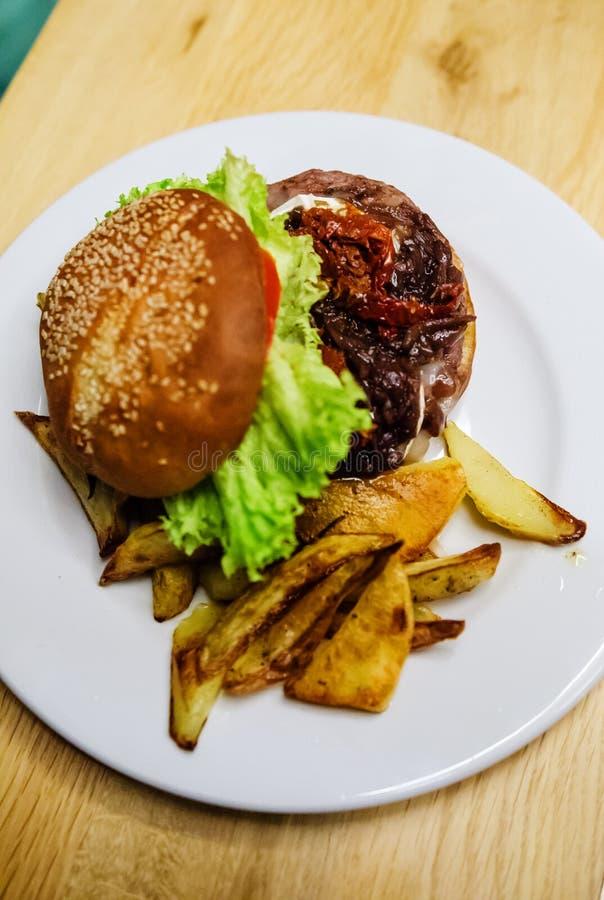 Hamburger de boeuf avec du fromage, tomates sèches image stock