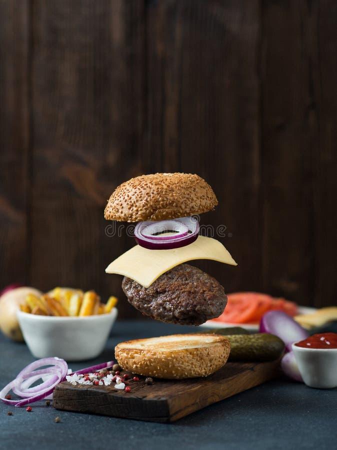 Hamburger de flottement de boeuf avec du fromage et l'oignon images stock