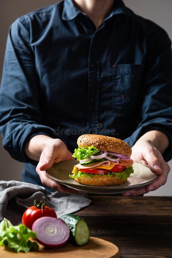 Hamburger de sandwich avec du jambon, le fromage et des légumes d'un plat dans des mains de l'homme Copiez l'espace Aliments de p image libre de droits