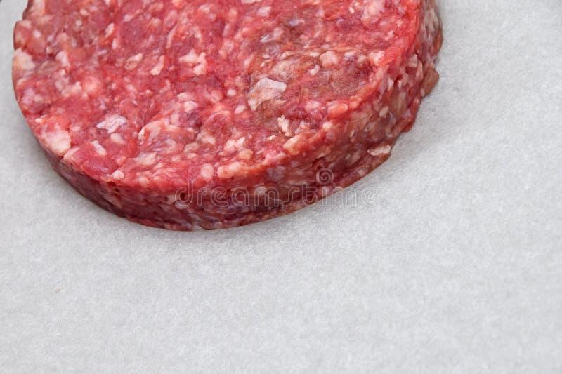 Hamburger de viande crue, hamburger sur le parchemin blanc photos libres de droits