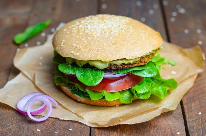 Hamburger del vegano, hamburger con il cece Patty, diffusione dell'avocado e verdure, pasto vegetariano fotografia stock