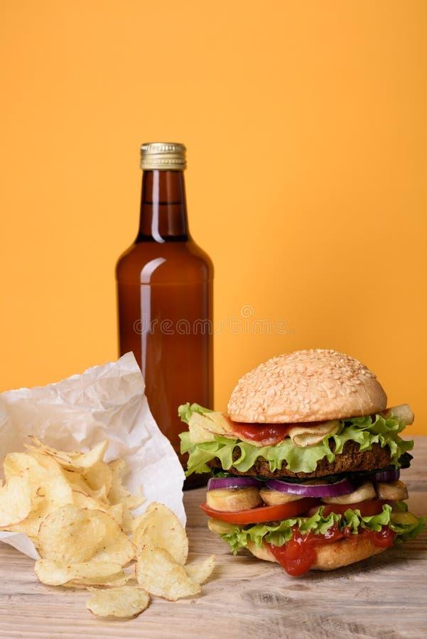 Hamburger delicioso com as microplaquetas da cerveja e de batata na tabela de madeira, fundo amarelo imagens de stock royalty free