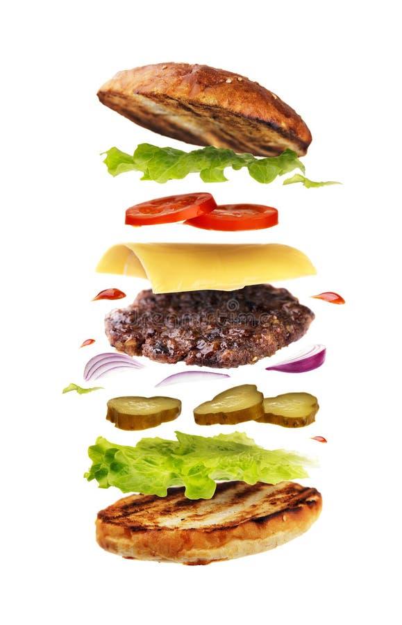 Hamburger delicioso com ingredientes do voo fotografia de stock royalty free