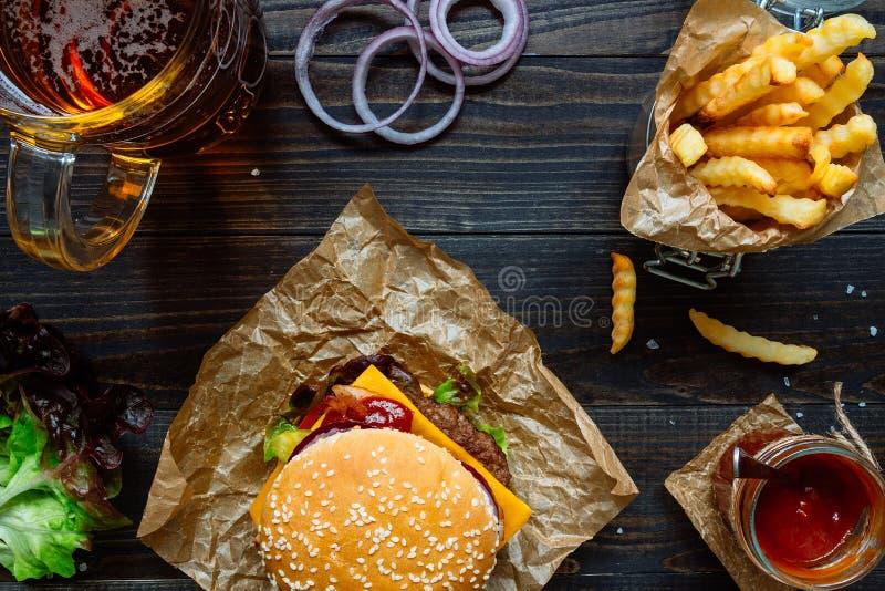 Hamburger deliziosi freschi con le patate fritte, la salsa e la birra sulla vista di legno del piano d'appoggio fotografie stock libere da diritti